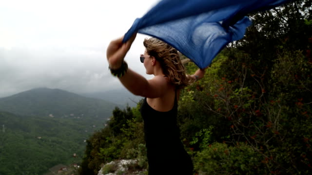 Young woman stands on rocky crest, scarf blowing in wind
