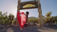 SLO MO. Young woman stands with a flowing red scarf in a rustic gateway in the Nevada desert.