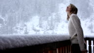 Young woman steps onto chalet veranda, watches snow flakes fall
