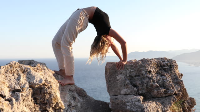 Young woman stretches between rocks, above sea