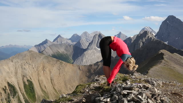 Young woman stretches, performs yoga moves on mountain summit