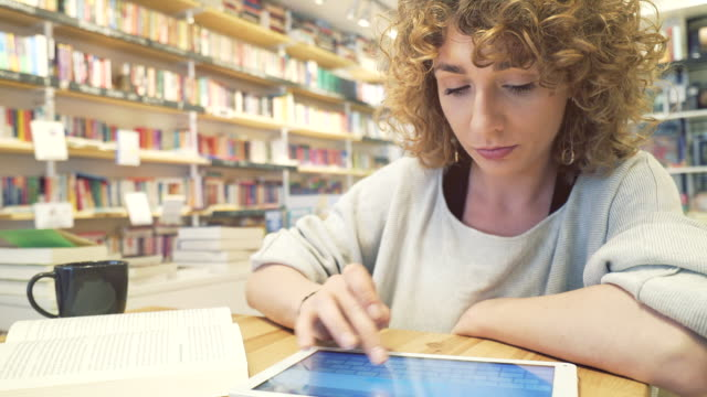 Young woman studying using a book and a digital tablet.