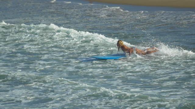 A young woman surfing in a bikini on a longboard surfboard. - Slow Motion