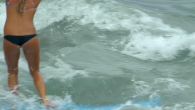A young woman surfing in a bikini on a longboard surfboard.