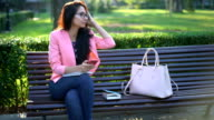 Young woman surfing the net on her mobile phone and relaxing in the park