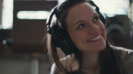 CU SLO MO. Young woman sways her head and smiles as she listens to music in headphones.