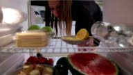 Young woman  takes orange juice, cheese, avocado from the fridge