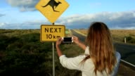 Young woman takes picture of kangaroo sign, Australia