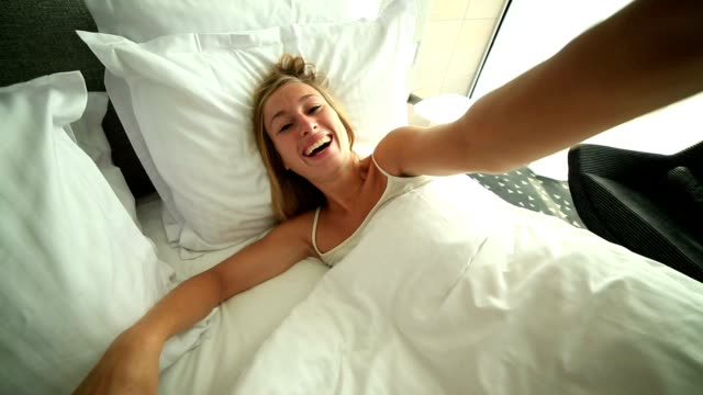 Young woman takes selfie in hotel room bed