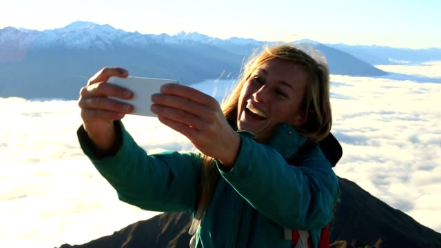 Young woman takes selfie on mountain summit