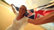 Ung kvinna tar selfie porträtt på stranden med australiska flaggan