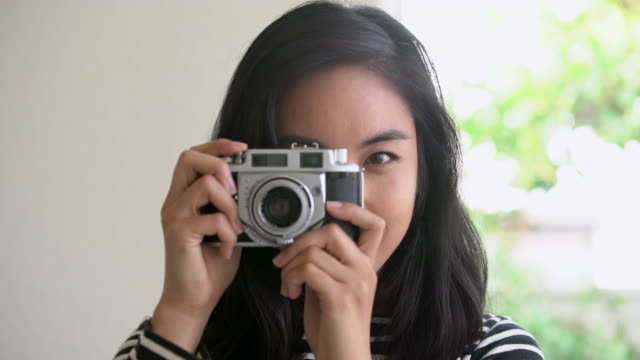 CU Young woman taking a photo with a vintage camera