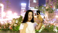 Young woman taking a selfie at night