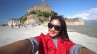 CNEUTRV1093 Young woman taking a selfie photo at Mont Saint Michel