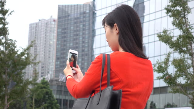 Young woman taking a selfie using phone