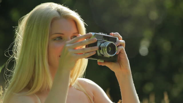 CU Young woman taking photographs outdoors / London, United Kingdom