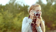 Young woman taking photos with retro camera