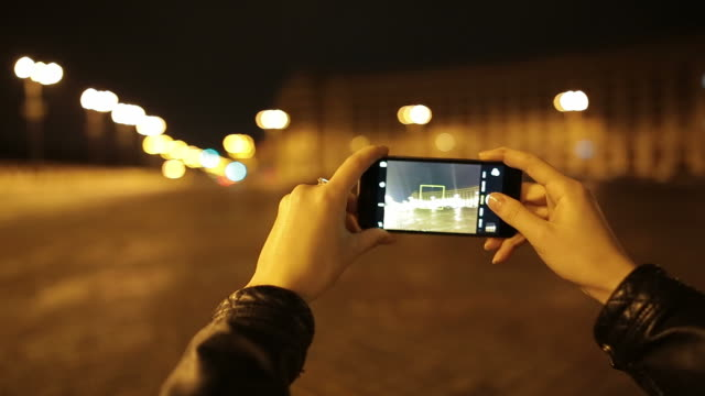 Young woman taking pictures in night time.
