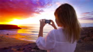 Young woman taking pictures of amazing sunset at beach