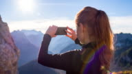 Young woman taking pictures of mountains with her smartphone