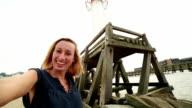 Giovane donna prendendo selfie con faro in Normandia