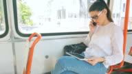 Junge Frau sprechen im Mobiltelefon, während Sie Ihre Digitaltablett in die Straßenbahn ein.