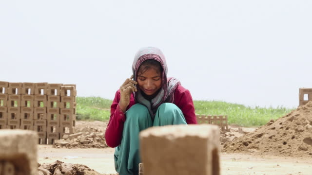 Young woman talking on a mobile at brick factory, Haryana, India