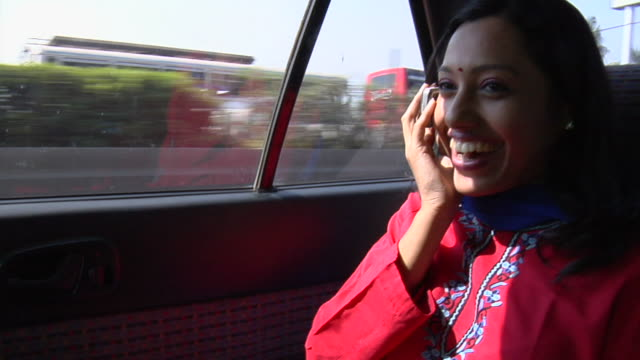 CU, Young woman talking on mobile phone on back seat of moving car, Mumbai, Maharashtra, India