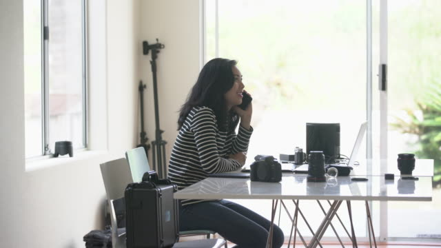 WS Young woman talking on the phone in her photography studio
