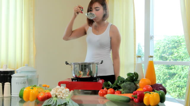 Young woman tasting soup