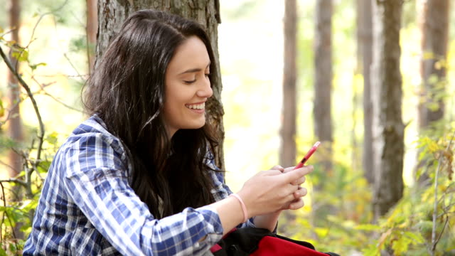 Young woman texting in the forest