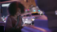 Young woman texts on smartphone and looks up at the neon city lights on busy Las Vegas street corner.