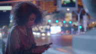 Young woman texts on smartphone on Las Vegas street corner at night as cars pass by.