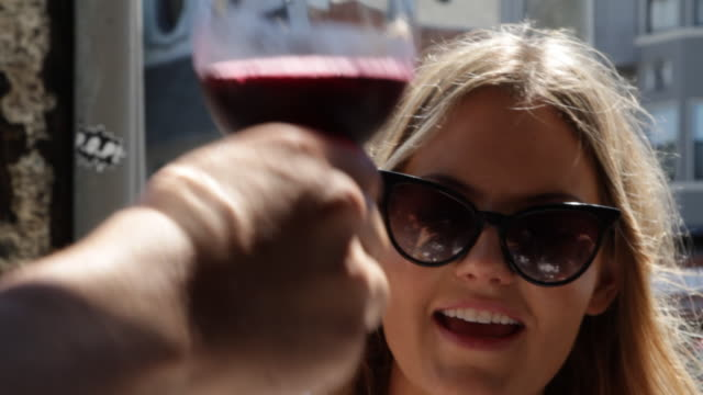 MCU Young woman toasting wine at cafe in San Francisco