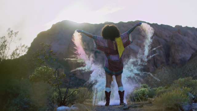 SLO MO. Young woman tosses colorful sand in the air and dances in scenic desert.