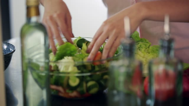 CU TD Young woman tossing salad in kitchen