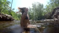 Jonge vrouw met natte haren in het water gooien