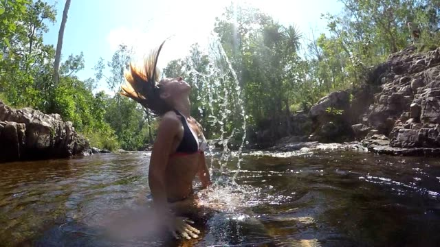 Young woman tossing wet hair in water