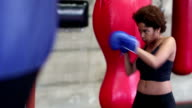 Young woman training at boxing in gym