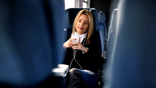 Young woman travel and listening music in train