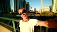 Young woman traveling in Toronto taking selfie portrait with cityscape