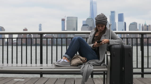 Young Woman Traveller Sitting on bench and Waiting