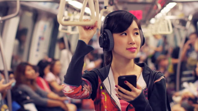 MS Young woman travelling on a train, listening to music