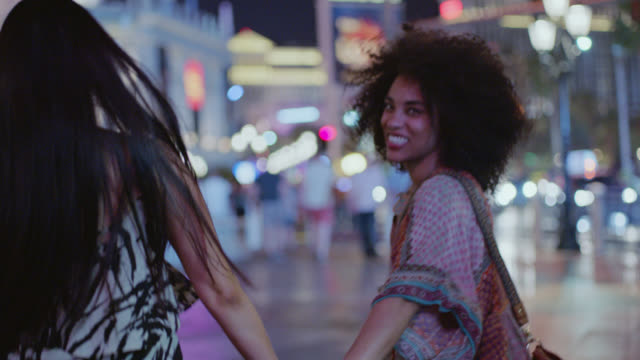 SLO MO. Young woman turns to laugh at camera as friends take off running hand in hand down Las Vegas strip at night.