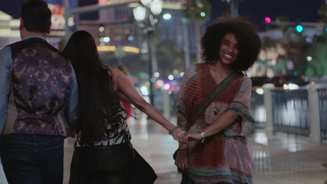 SLO MO. Young woman turns to laugh at camera as friends walk hand in hand down Las Vegas strip at night.
