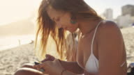 MS A young woman types on her smartphone on Ipanema Beach / Rio de Janeiro, Brazil