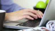 Young woman typing on laptop keyboard.