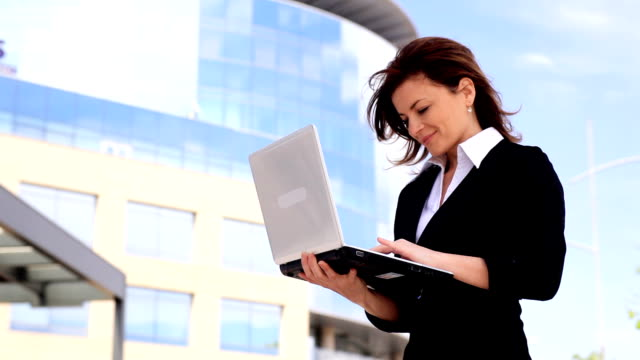 Young woman typing on laptop, standing outdoor.