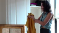 Young Woman Unpacks Clothes in New Apartment