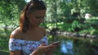 Junge Frau mit einem Mobiltelefon im Park